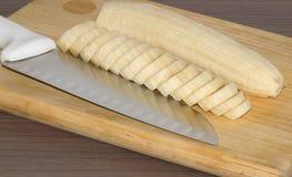 Plátano y cuchillo cortados Fotografía de archivo libre de regalías