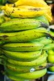 Plátanos amarillos y verdes en el mercado Imágenes de archivo libres de regalías