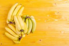 Plátanos amarillos y verdes en un tablero amarillo al lugar correcto FO Imágenes de archivo libres de regalías