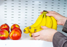 Plátanos de la toma de las manos de estantes de una tienda Imágenes de archivo libres de regalías