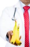 Plátanos de ofrecimiento del doctor Imágenes de archivo libres de regalías