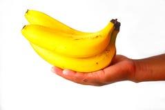 Plátanos en mano negra Fotos de archivo libres de regalías