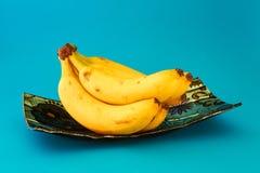 Plátanos frescos en un plato azul foto de archivo