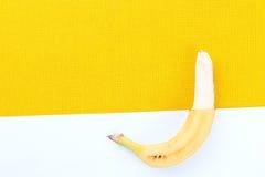 plátanos maduros amarillos Mitad-hendidos de las zonas tropicales en un blanco y Foto de archivo