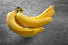 Plátanos maduros en fondo gris Fotografía de archivo