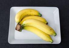 Plátanos maduros en la placa blanca Fotos de archivo libres de regalías