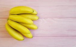 Plátanos maduros en un antioxidante de madera rosado del postre Imagenes de archivo