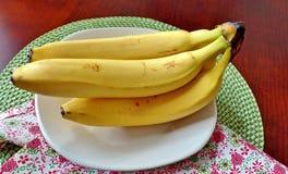 Plátanos maduros en una placa blanca Foto de archivo