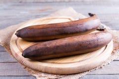 Plátanos maduros en una tabla de cortar Fotos de archivo libres de regalías