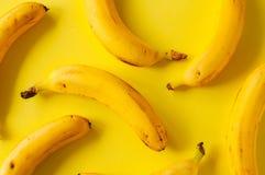 Plátanos maduros frescos en un fondo amarillo imagen de archivo libre de regalías