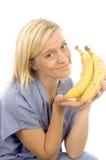 Plátanos maduros sanos sonrientes del doctor de la enfermera Fotos de archivo libres de regalías