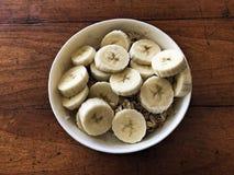 Plátanos y cereal en cuenco en la tabla Fotos de archivo libres de regalías