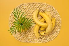 Plátanos y hojas de palma maduros en fondo amarillo Foto de archivo