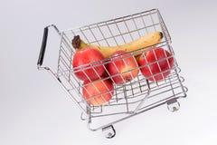 Plátanos y manzanas de compra del supermercado Imágenes de archivo libres de regalías