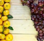 Plátanos y uvas en el piso de madera Imagen de archivo libre de regalías