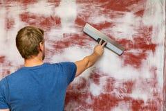 Plâtrant le mur avec attacher du ruban adhésif au couteau photos stock