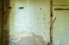 Plâtre intérieur de mur de maison avec des trous et des dommages de balle de shrapnel de grenade Image libre de droits