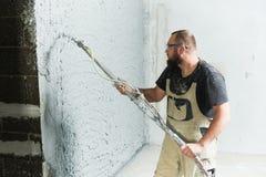 Plâtrier employant le mortier de pulvérisation de plâtre de mastic de screeder sur le mur image libre de droits