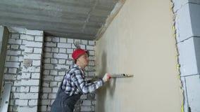 Plâtrier lissant le plâtre sur le mur intérieur avec la règle de construction banque de vidéos