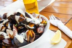 Plätera mycket av musslor med vitlöksås på tabellen Arkivbild