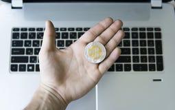 Plätschern Sie Münze auf einer Laptoptastaturnahaufnahme auf einer Bergmannhand Blockchain-Bergbau Digital-Geld und virtuelles cr Stockbild