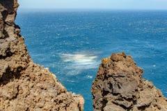 Plätscherndes Meer mit Felsen und farbigen Wasserwinden lizenzfreie stockfotos