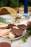 Plätzchen, blaue Kerze, Tannenzweig, Verzierungen und Kieferkegel auf hol Stockfoto