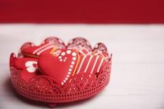 Plätzchen in der Herzform im roten Hintergrund Lizenzfreie Stockfotografie