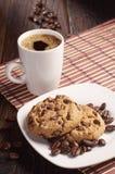 Plätzchen in der Platte und in der Kaffeetasse Stockfotos
