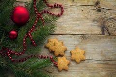 Plätzchen in der Sternform und Tannenzweige mit Weihnachtsflitter an Lizenzfreie Stockfotos