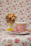 Plätzchen in einem Weidenkorb und in einer Tasse Tee Stockbilder