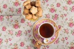 Plätzchen in einem Weidenkorb und in einer Tasse Tee Stockbild