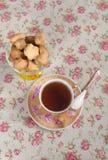 Plätzchen in einem Weidenkorb und in einer Tasse Tee Lizenzfreies Stockbild