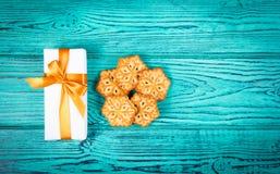 Plätzchen in Form der Schneeflocken Gebäck in Form der Schneeflocken und eines Weihnachtsgeschenks Geschenke und Feiertage Lizenzfreies Stockbild