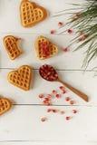 Plätzchen in Form von Herzen auf einem Holztisch Lizenzfreies Stockfoto