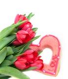 Plätzchen in Form von Herzen und roten Tulpen Lizenzfreie Stockfotografie