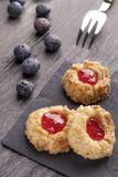 Plätzchen gemacht von Haselnuss Shortcake mit Erdbeermarmeladeninnere auf einer schwarzen Serviette mit Blaubeeren stockfotografie