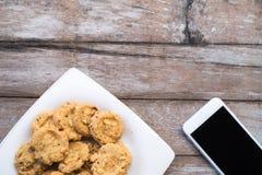 Plätzchen im Teller und im Telefon auf Holztischhintergrund Stockfotografie