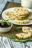 Plätzchen mit Käse, Oliven und Rosmarin auf Serviette Stockfoto