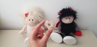 Plätzchen mit roter Füllung gegen Doppelromantische Spielwaren des engels und des Dämons stockfoto