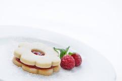 Plätzchen mit Stau auf weißer Platte mit Himbeeren, Kuchen auf weißer Platte, tadellose Dekoration, Konditorei, Süßspeise, Kuchen Stockbild