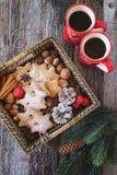 Plätzchen mit zwei Tasse Kaffees und Weihnachtszimt im Korb lizenzfreie stockbilder