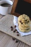 Plätzchen-Schokoladensplitter mit Kaffee und schwarzes Brett auf Jutefaser, Frühstück, neuer Morgen Lizenzfreies Stockbild
