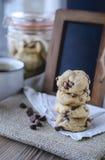 Plätzchen-Schokoladensplitter mit Kaffee und schwarzes Brett auf Jutefaser, Frühstück, neuer Morgen Stockbild