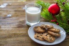 Plätzchen und Milch für Weihnachtsmann auf hölzernem Hintergrund Lizenzfreie Stockfotos