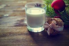 Plätzchen und Milch für Weihnachtsmann auf hölzernem Hintergrund Lizenzfreie Stockbilder