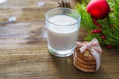 Plätzchen und Milch für Weihnachtsmann auf hölzernem Hintergrund Stockbild