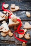 Plätzchen-Valentinstagkarten mit roter Reihe auf Holztisch Lizenzfreie Stockbilder