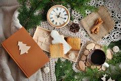 Plätzchen-, Weihnachtsnadeln, Tasse Tee Uhr und Niederlassungen, Zimtstangen auf altem Holztisch Lizenzfreies Stockbild