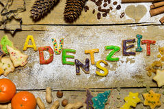Plätzchenbuchstaben mit Weihnachtsdekoration auf Holz, deutsches Wort Stockbild